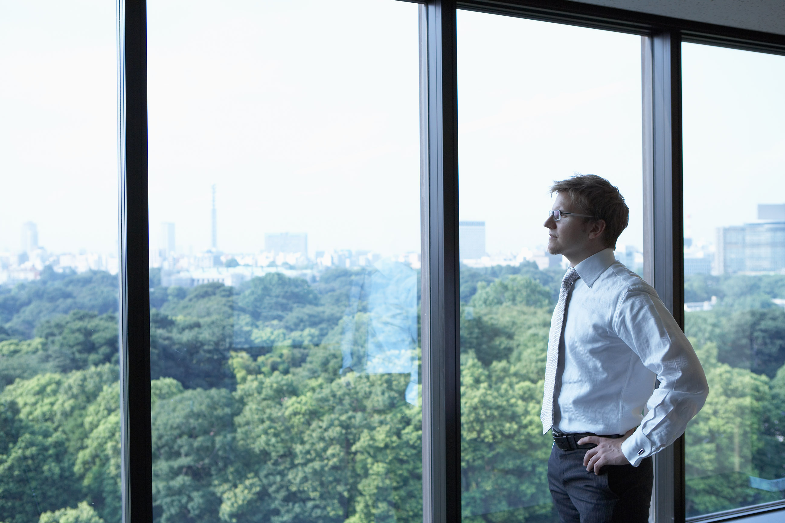 Businessman Looking out Window --- Image by © BASE/Corbis