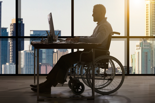 Business man sitting in wheelchair at a desk in an office, laptop open on the desk in front of him, hands on the keyboard of the laptop