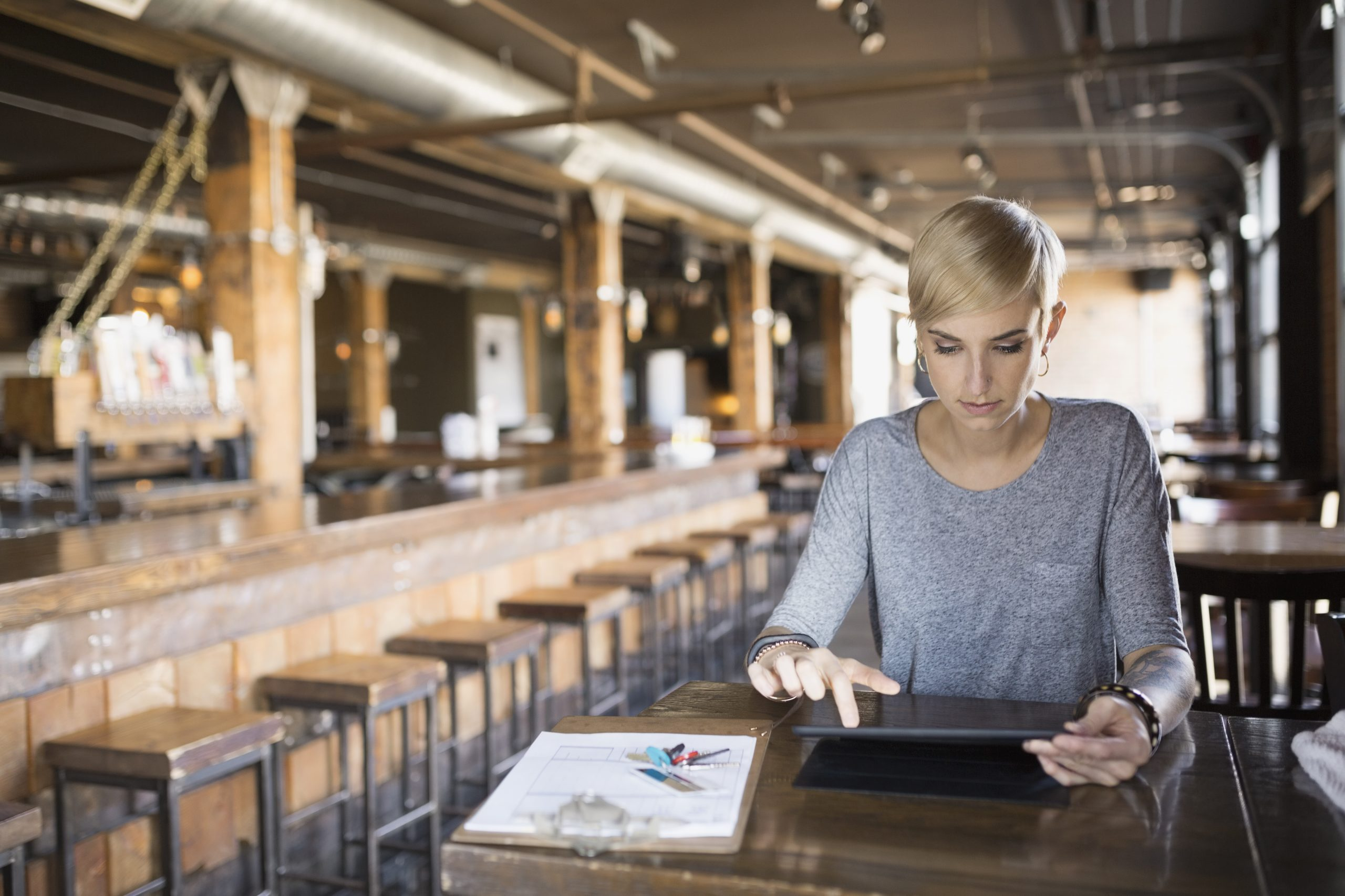Pub owner using enterprise analytics on tablet at table